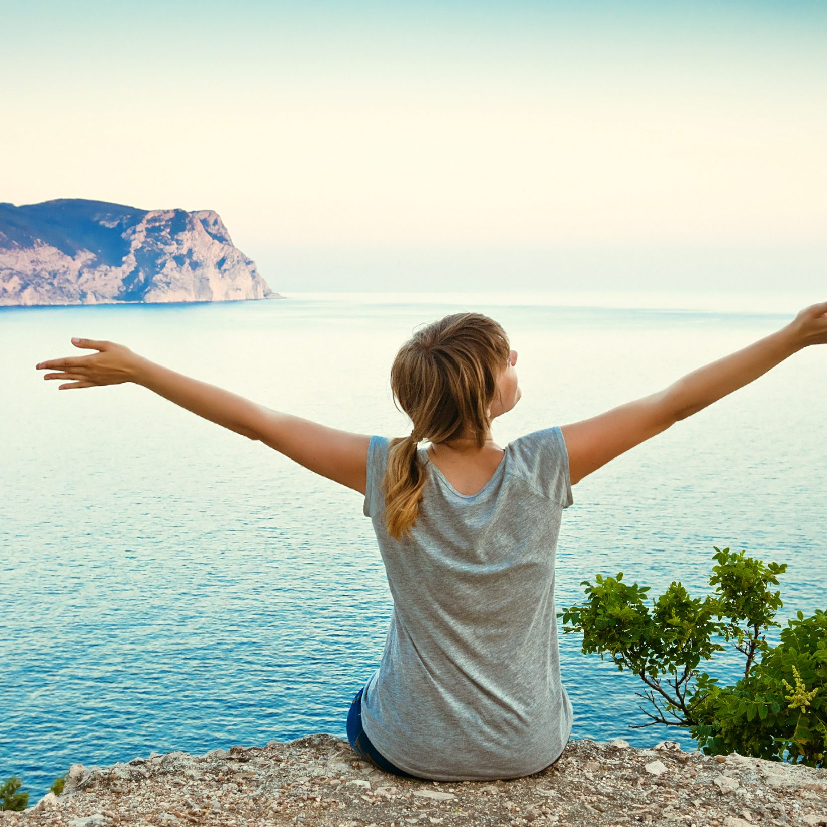 girl sits on a hill with raised hands and looking at the sea